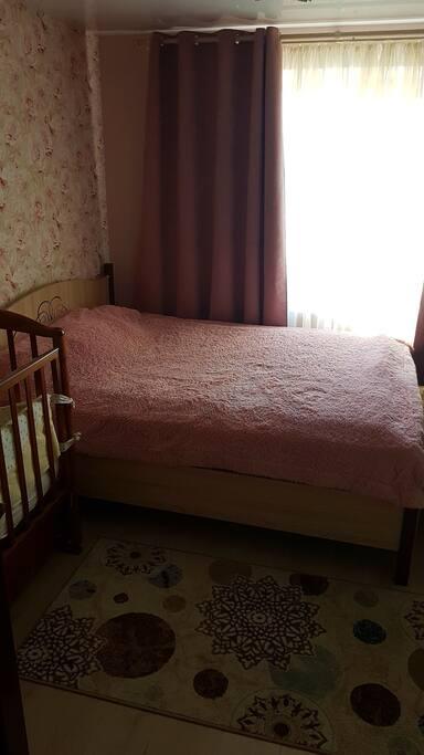 спальная комната, в которой есть 2ух спальная кровать так же телевизор и детская кроватка для малыша если понадобится