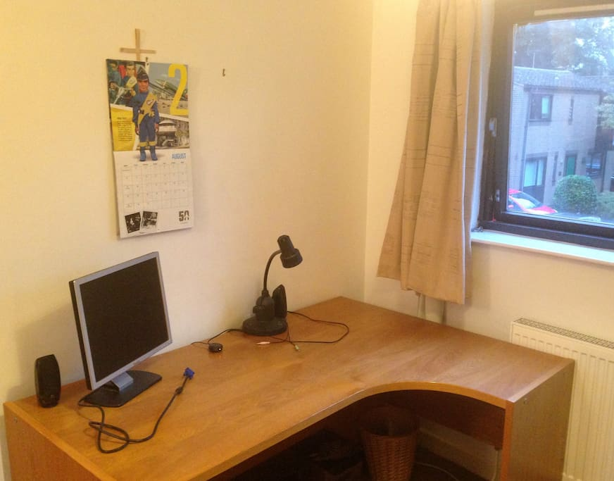 Office-size desk with extra monitor, sound and reading lamp. Bright window.