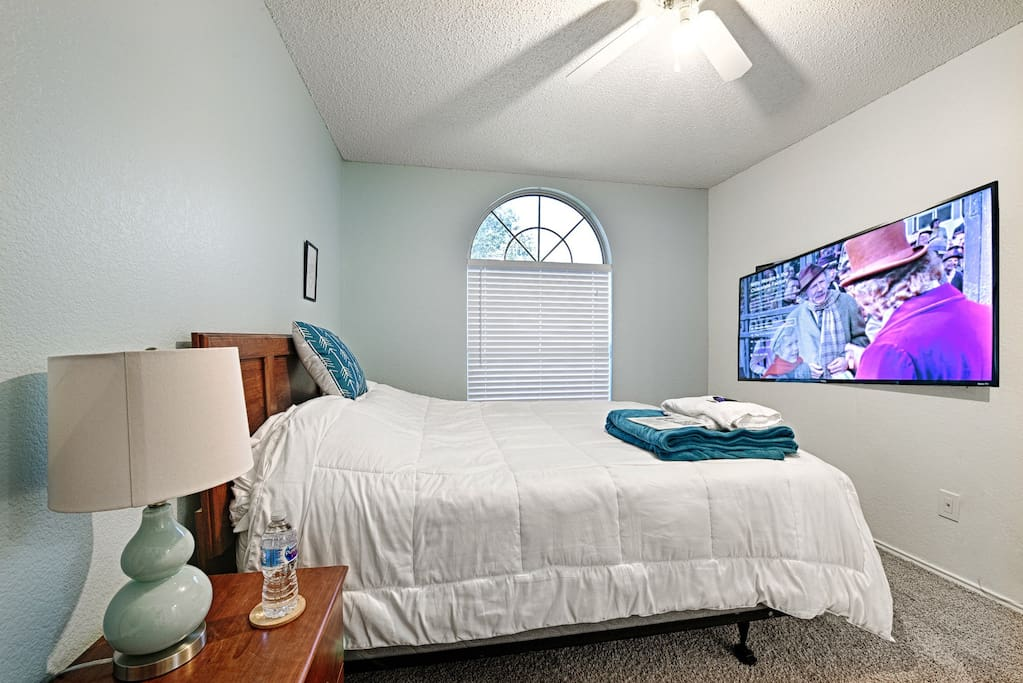 Bedroom features luggage rack, large mirror, and 4K TV with Cable and Netflix