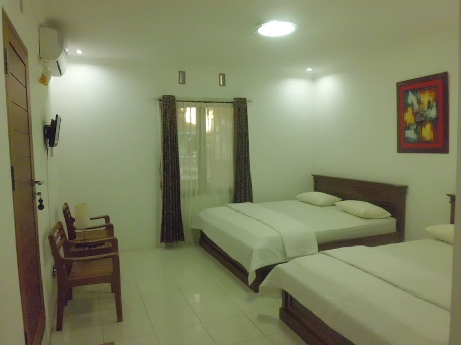 Spacious Bedroom with Air Conditioning, Flat TV and Toilet.