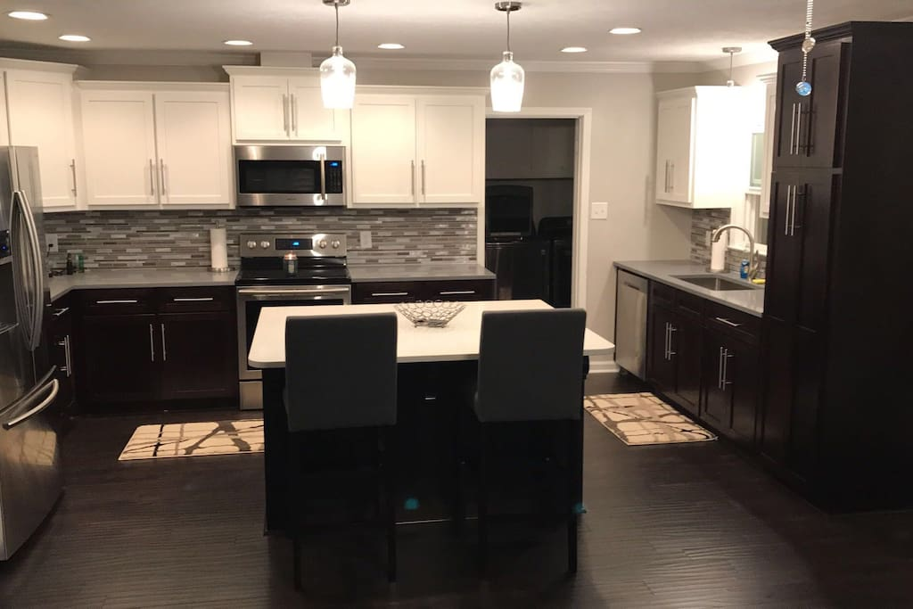 Spacious Kitchen with wine fridge in the Island.  2 Bar stools, Laundry room through single door, and all new appliances.