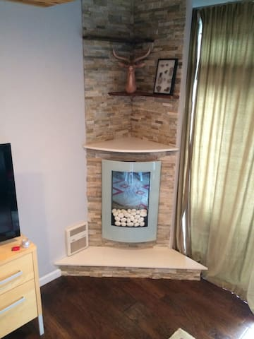 Modern fireplace with white river rock and ledge stone face and live edge acacia wood shelves