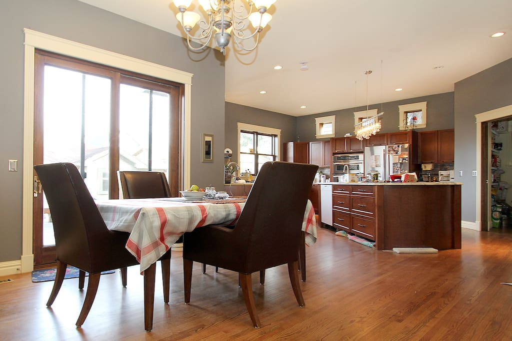 Dining area with table with kitchen and deck in background