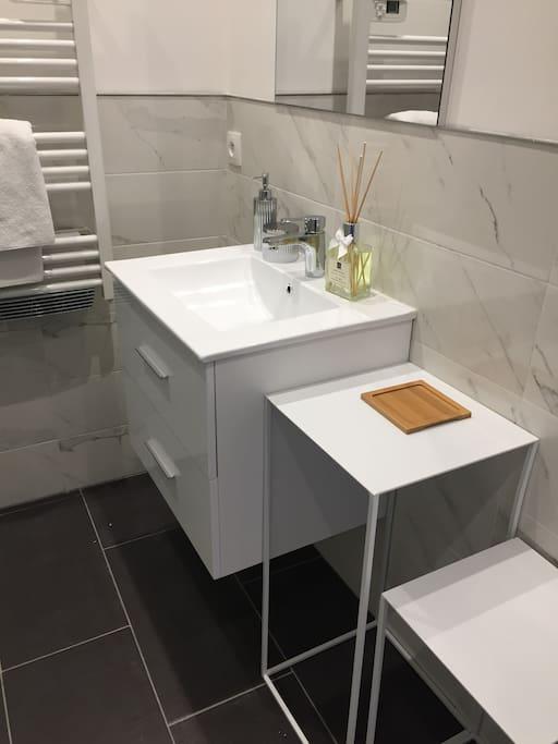 Salle de bain avec douche, WC, sèche serviette, sèche cheveux, produit d'hygiène, serviettes de toilettes et sortie de douche.