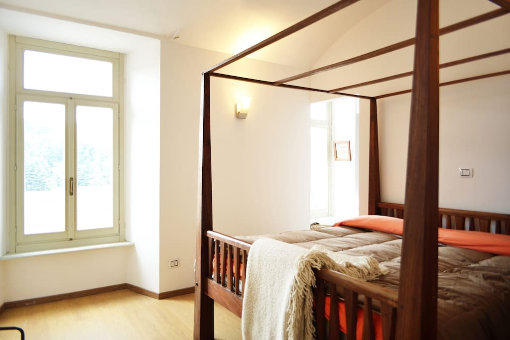 Bedroom with  poster king size bed and Alps view