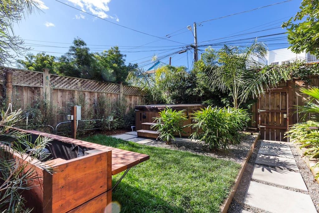 The lush yard designed by award-winning Flora Grubb Gardens includes a shared 4-person hot tub.
