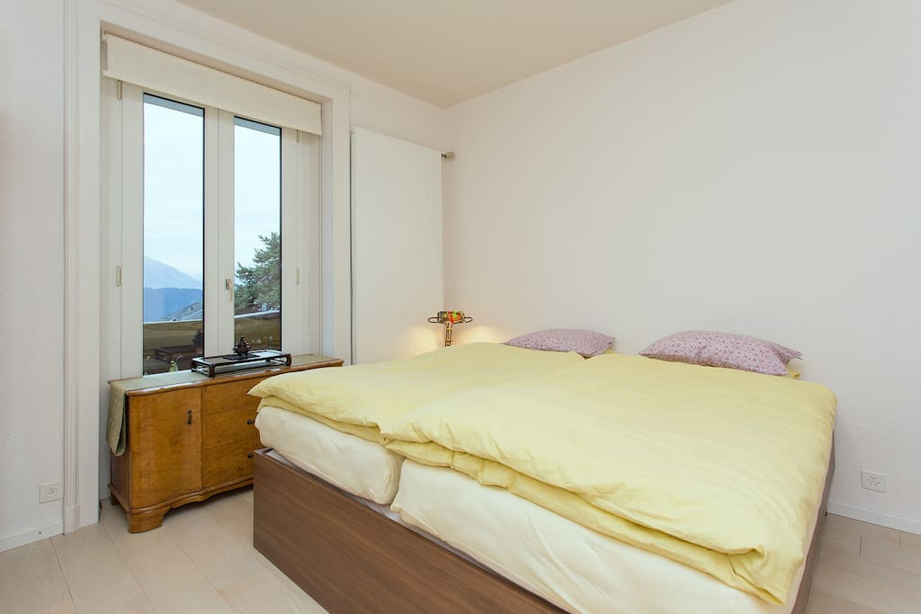 Master bedroom picture of double bed and Swiss Alps view.
