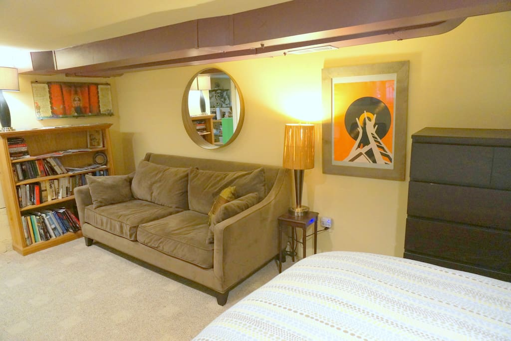 The room includes a full-size couch for relaxing and a bookcase stocked with various guidebooks about Seattle and the surrounding area. If you're traveling with a third guest, the couch can transform into a comfortable bed with the back cushions removed.