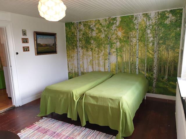 Soveværelse mod syd, pyntet med skovtapet på endevæggen.