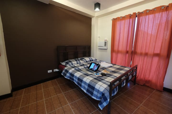 Queen sized bed, air conditioning unit, curtains, floor and wall space