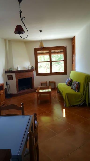 Salón con chimenea , sofá cama, mesa elevable , y mesa para comer plegable de hasta 6 personas   y tv ( USB )