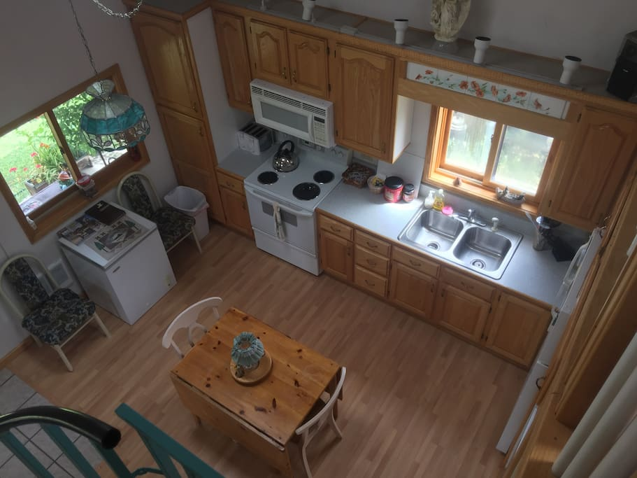 View of full kitchen from loft. Fully equipped. Table has fold out sides to make a larger table.