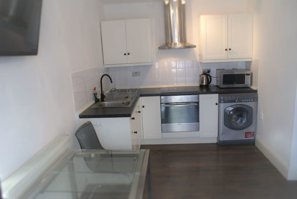 Kitchen with oven, washing machine, microwave, plates, glasses, mugs and cutlery, sink and hob.  Wall mounted TV on right