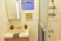 Clean, spacious bathroom stocked with supplies.