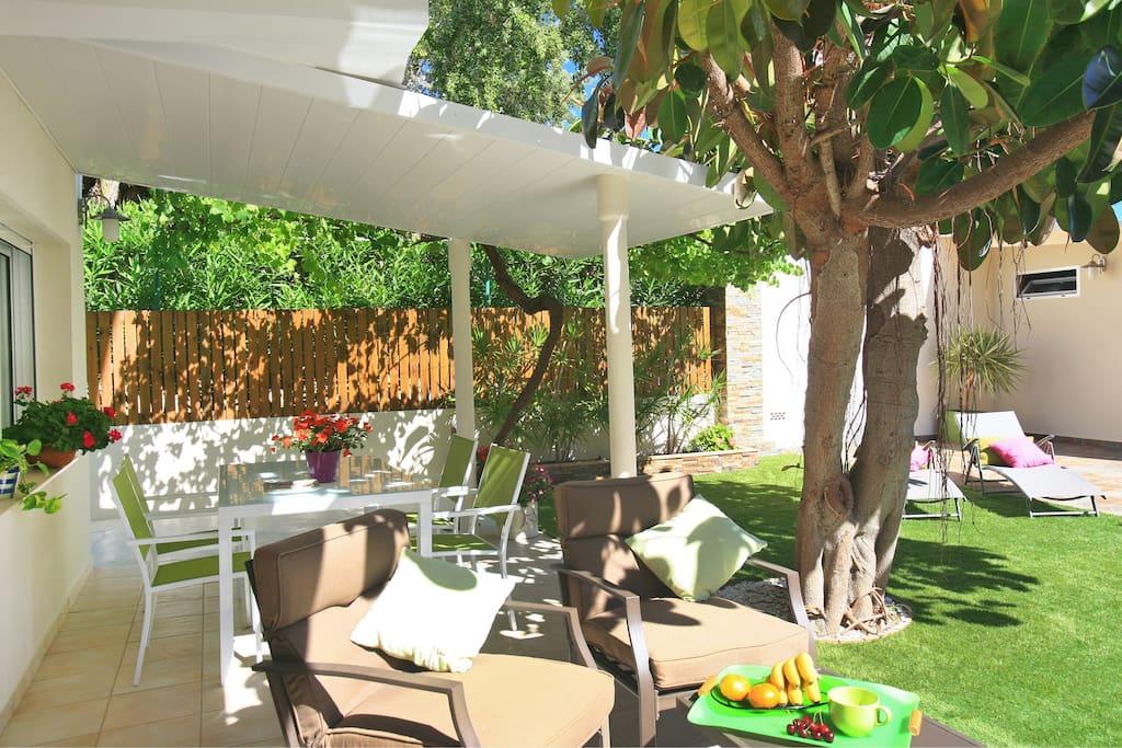 Terraza cubierta con dos ambientes. Zona para comer 4 comensales. Zona sofás.