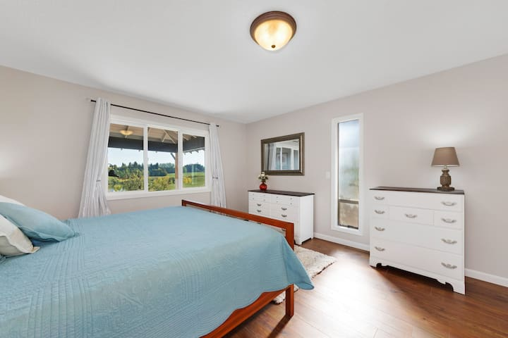 The master bedroom has a king size bed, two full size dressers and a beautiful view of the farmland outside.