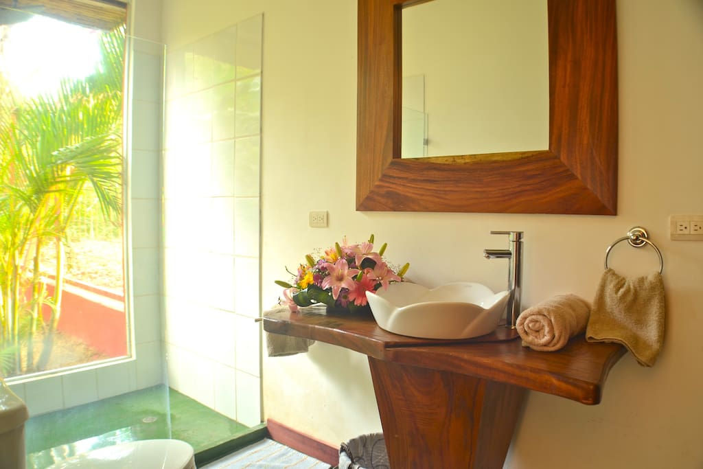 Twin bedroom ensuite bathroom -  Costa Rican wood carved by local artisans and an inside out shower .