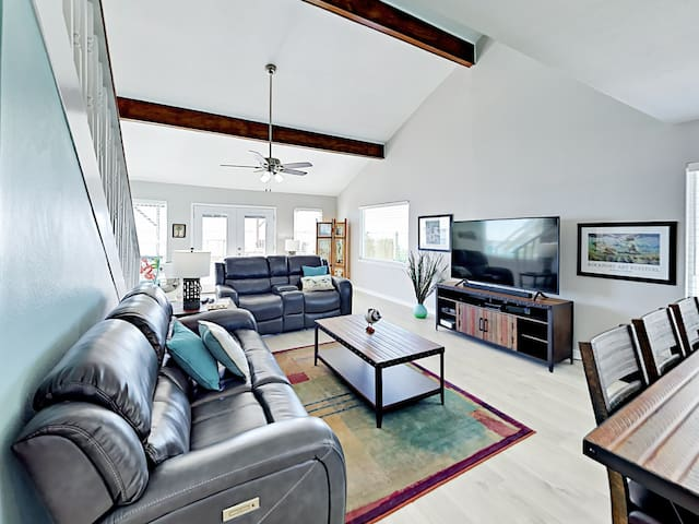 Relax on a sofa and reclining love seat below high ceilings in the open-concept living room.