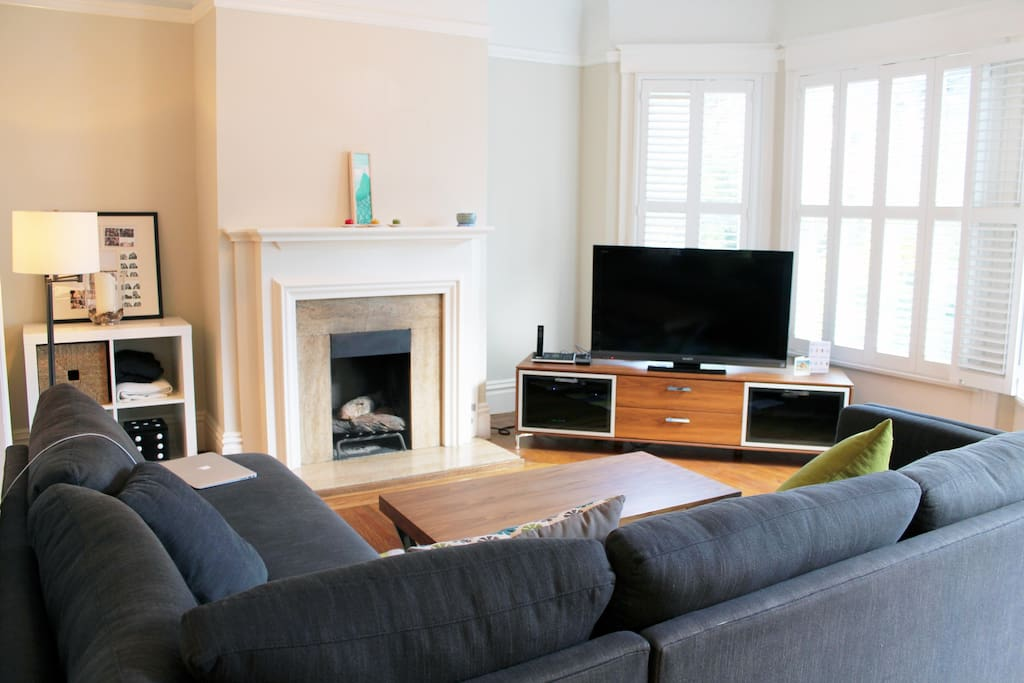 Bright clean living room with fireplace, cable tv and record player