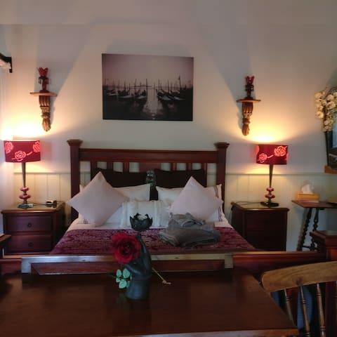 Studio style, spacious bedroom.   Panoramic windows, with views out to the established English style garden.