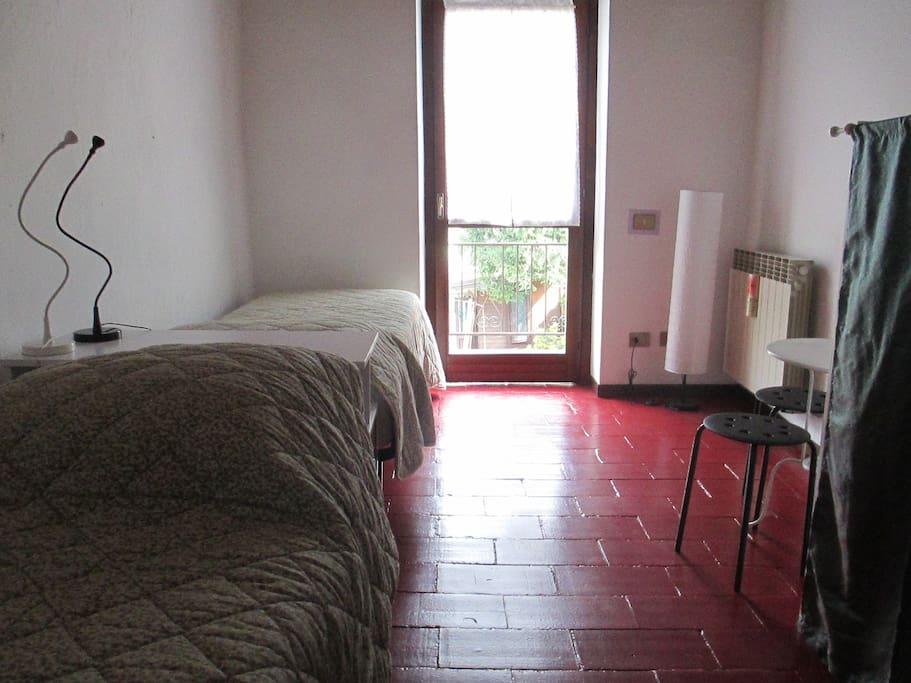 La camera doppia con letti singoli con un balcone che si apre sul giardino