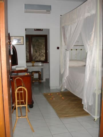"""One of the three bedrooms. All rooms have air conditioning and an ceiling fan. Wide king size beds with a rectangular """"kelambu""""."""