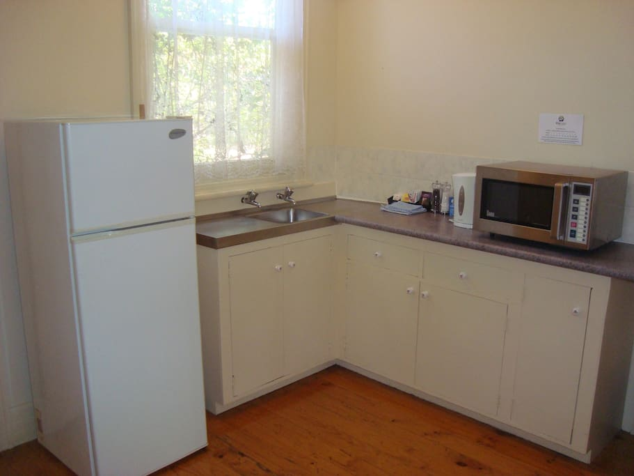 Unit 4's kitchen has a full size fridge, microwave, kettle, electric frypan, sandwich press, crockery, cutlery and plates.
