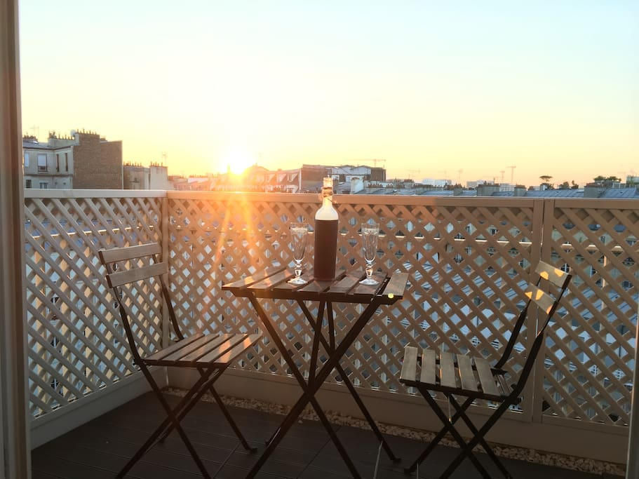 Enjoy the sunset and the Parisian rooftops with a glass of wine on a large balcony.