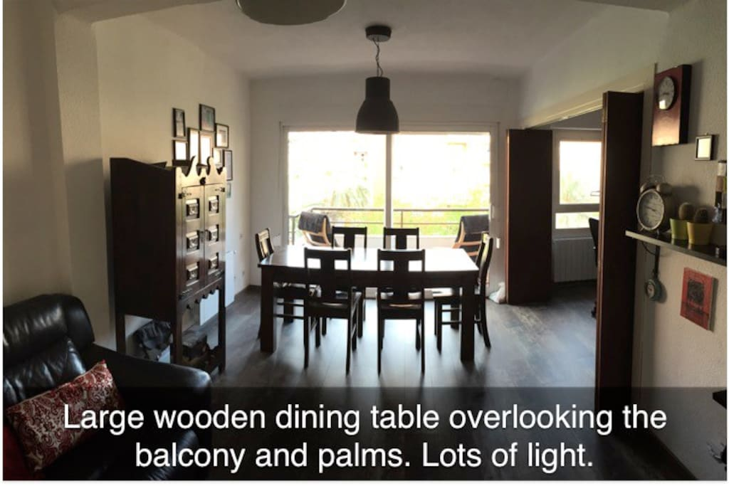 Large wooden dining table overlooking the balcony and palms. Lots of light.