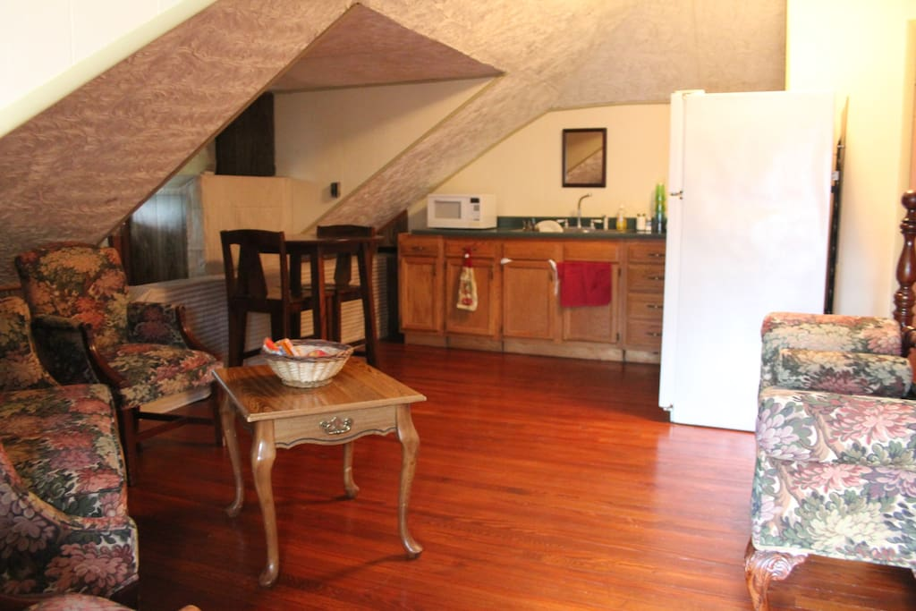 Your cozy attic guest suite: kitchenette, comfy sitting area, and queen-sized bed