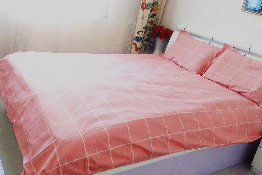 Queen-size bed with brand-new pink sheet and pillows