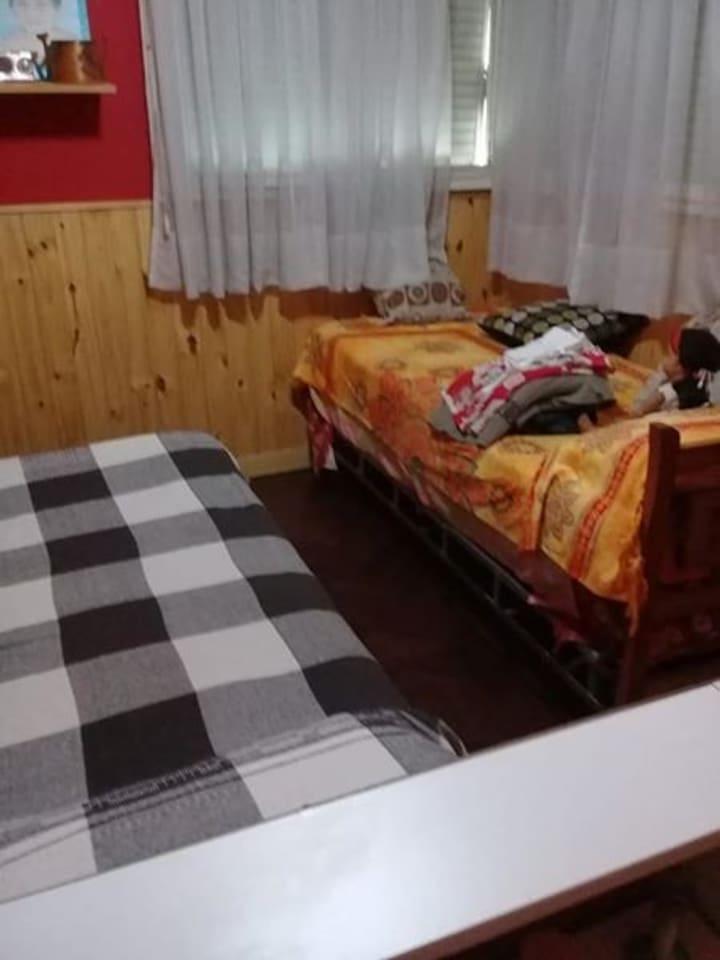 habitacion cuenta con cama 2 plaza, 1 de 1 plaza, placard, calefactor, ventilador de techo y televisor