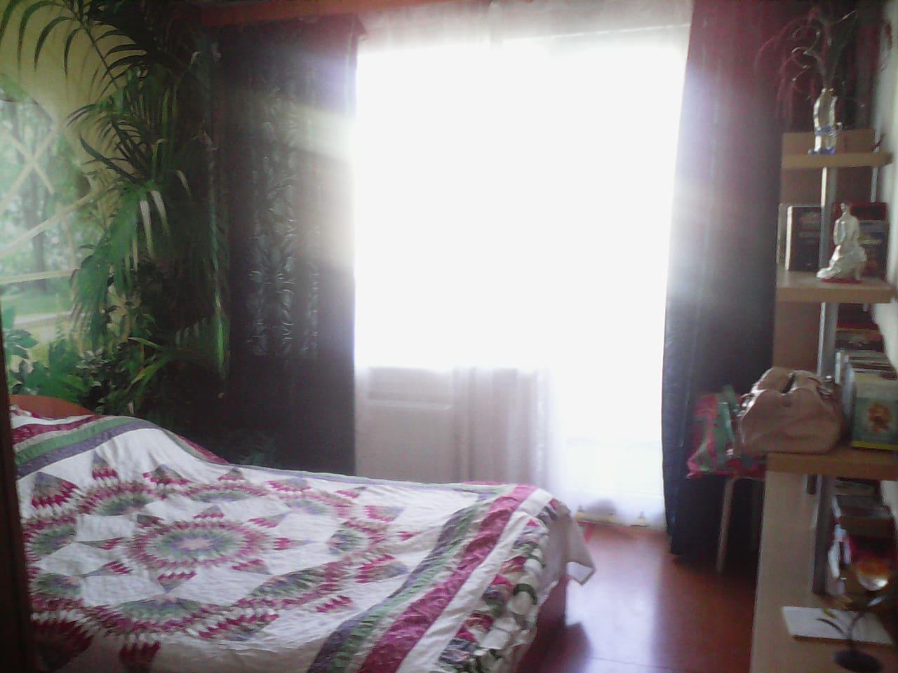Солнечная по утрам спальная комната  с двуспальной кроватью и выходом на балкон