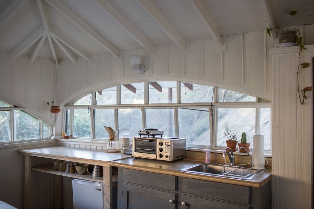 Kitchen space w mini fridge, small oven, toaster, and burner
