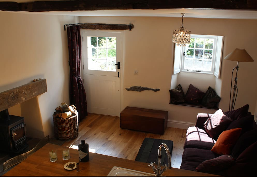 Cosy sitting room with log stove glowing, shutters closed, a perfect setting for you and your partner.