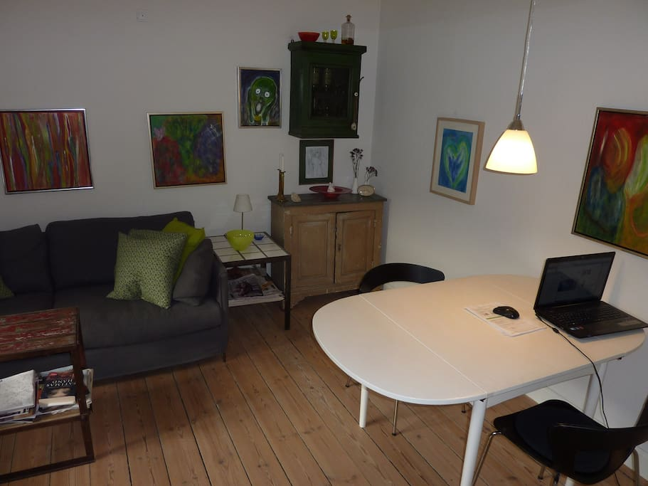 Rummelig stue med spisebord og sofa.