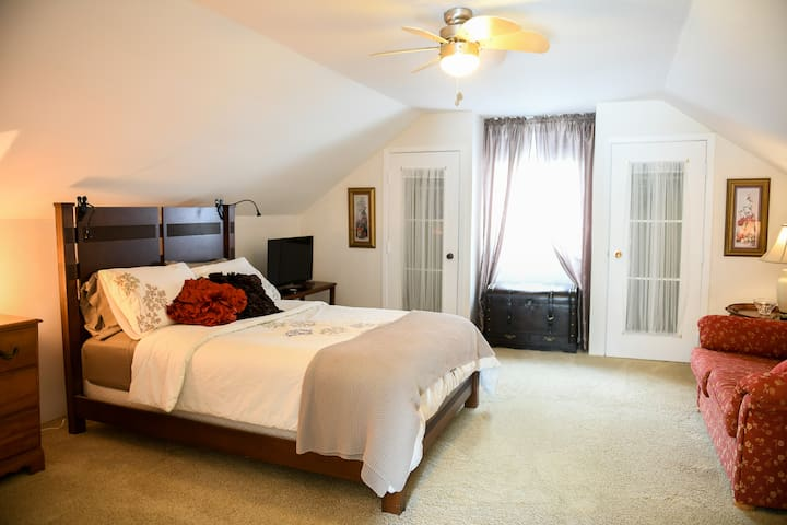 Grande chambre à l'étage, lit double, coin causeuse, et télé sans-fil. Large upstairs bedroom, double bed, loveseat and wireless T.V.