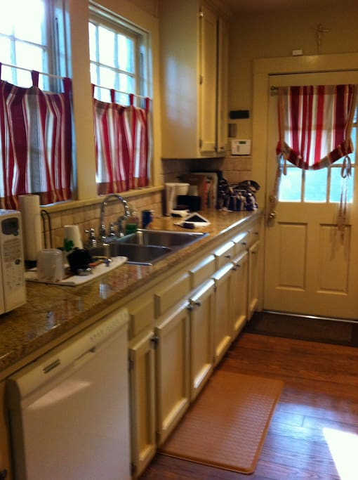 Kitchen with refrigerator, dishwasher, gas stove and oven, microwave and coffee pot