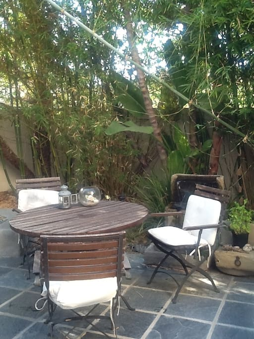 A backyard with a bamboo sanctuary-feeling. Bubbling waterfall and firepit included.
