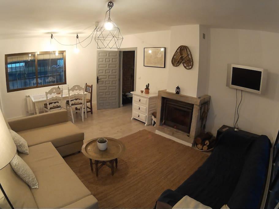 Salón con chimenea y sofá cama