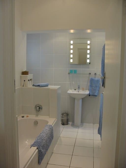 The fresh and bright bathroom with bath and walk - in shower.