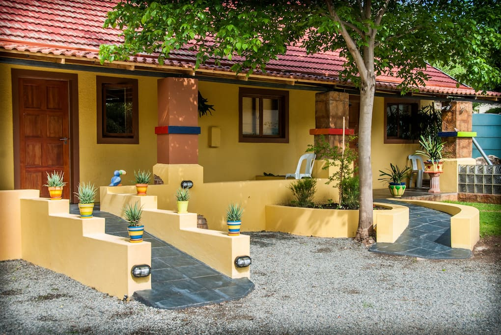 View of front 3 rooms accessible from parking with a fountain and desert plants in abundance