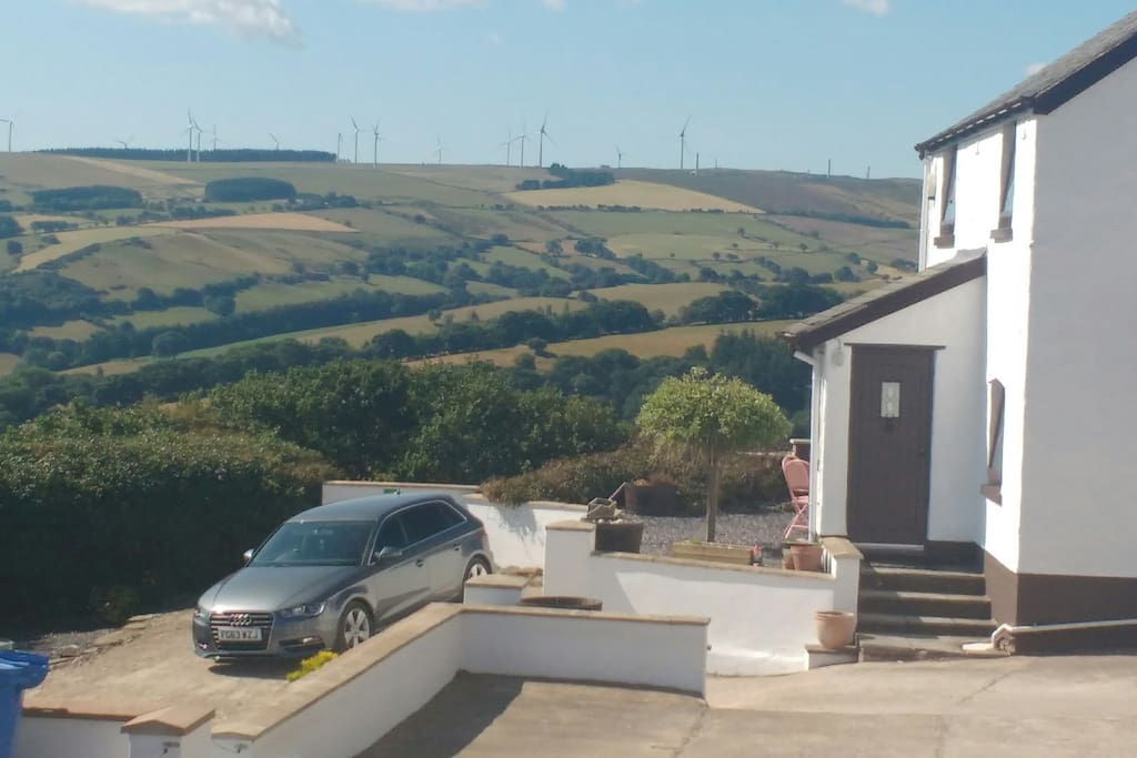 One of car parking areas at front of house with Brenig Wind farm on hill beyond.