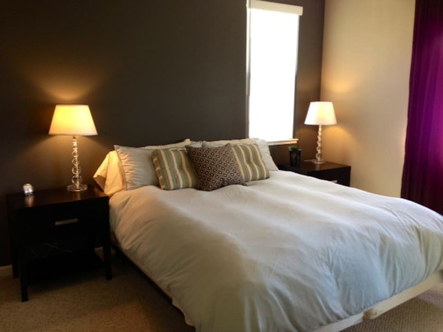 Plush Cal-King sized bed with large walk-in closet and door leading to balcony