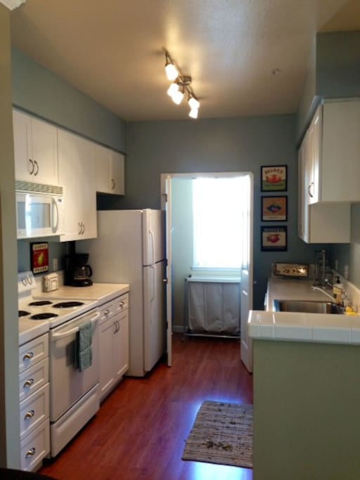 Fully stocked kitchen with double door entry to in-unit laundry facilities