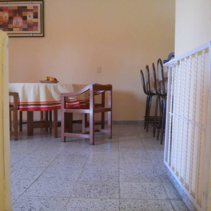 Mesa y barra para cuatro personas. Las escaleras tienen puerta para mantener protegida la sala en caso de haber niños pequeños.