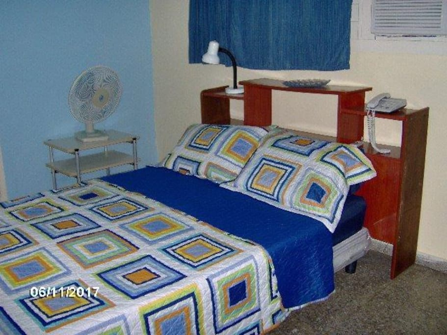 Room 1. Queen size bed, AC, fan and storage space