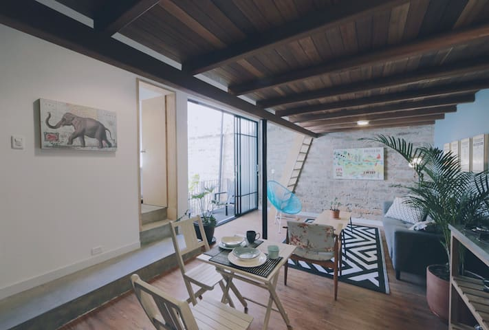 Cozy space with small dining room, kitchenette, living room, private bathroom, private balcony and stairs to the mezzanine / dormitory