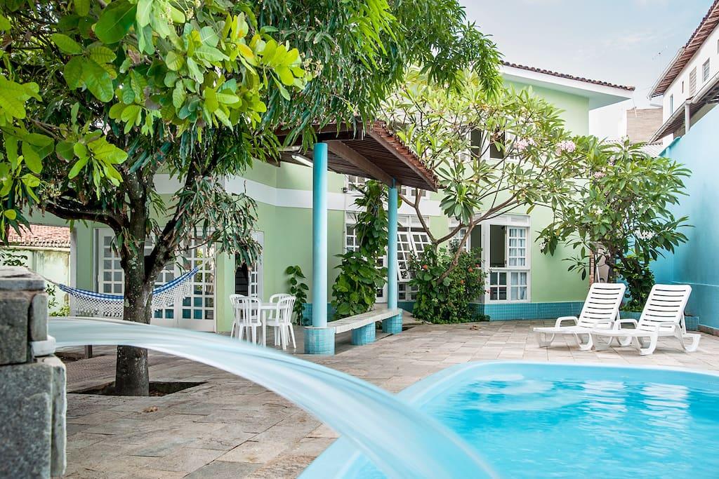 Cascata, piscina e vegetação.