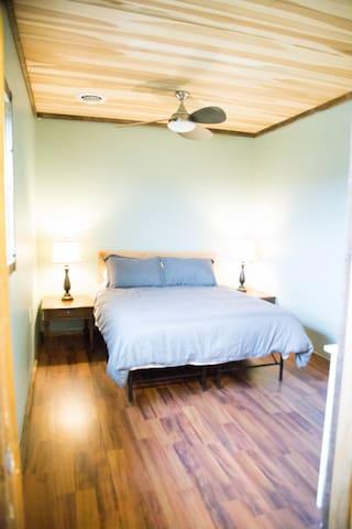 Main Bedroom, with queen bed, large dresser, nightstands and fan.